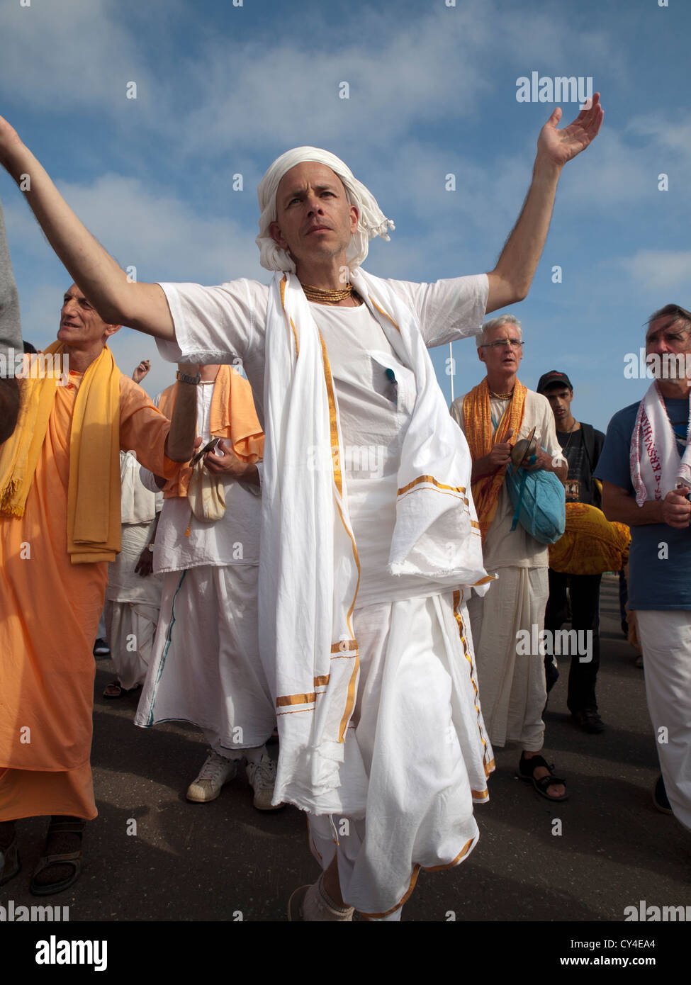 Members of the Hare Krishna movement gather to sing and dance on the seafront at Brighton. - Stock Image