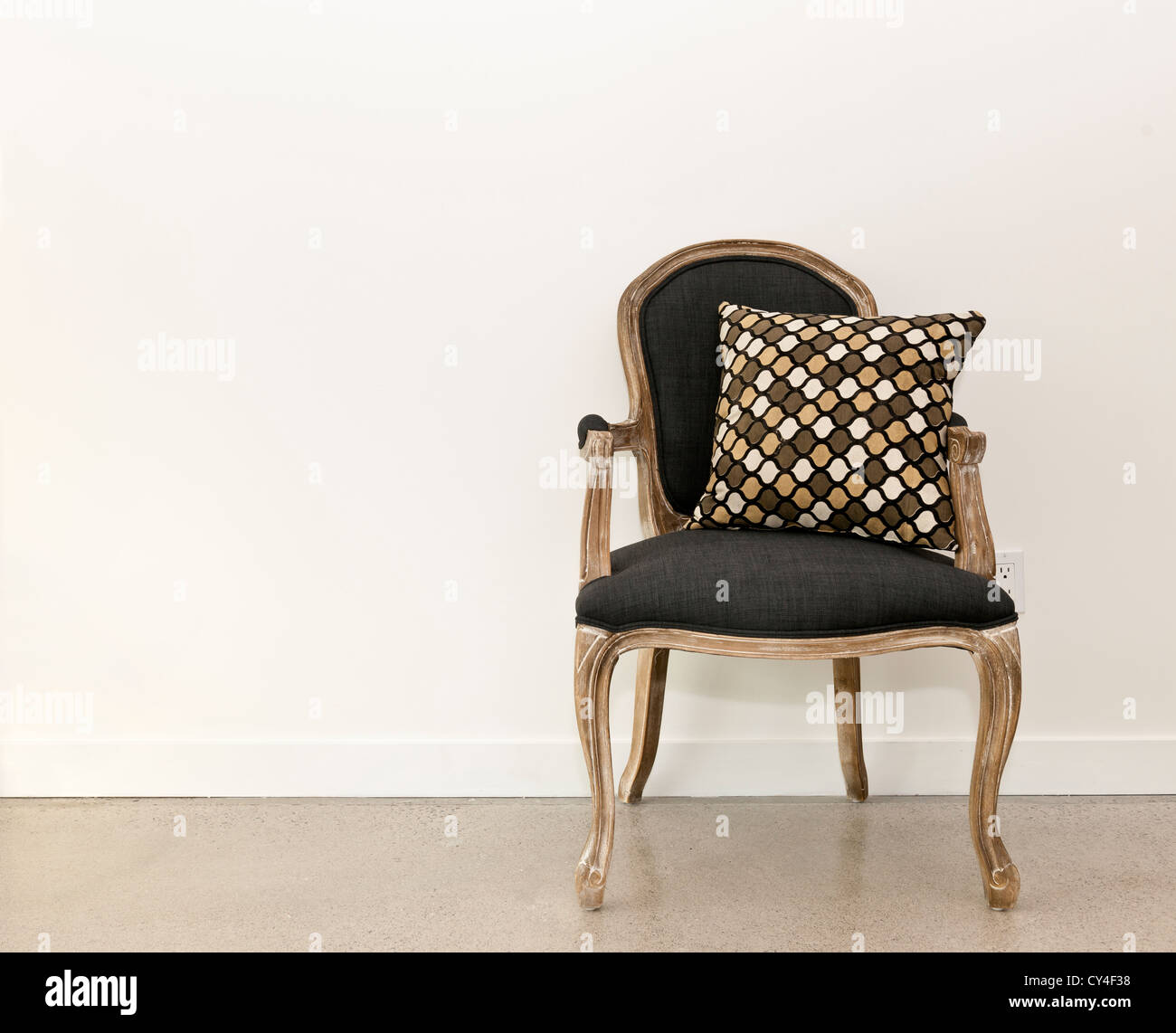 Antique armchair furniture with cushion against white wall - Stock Image