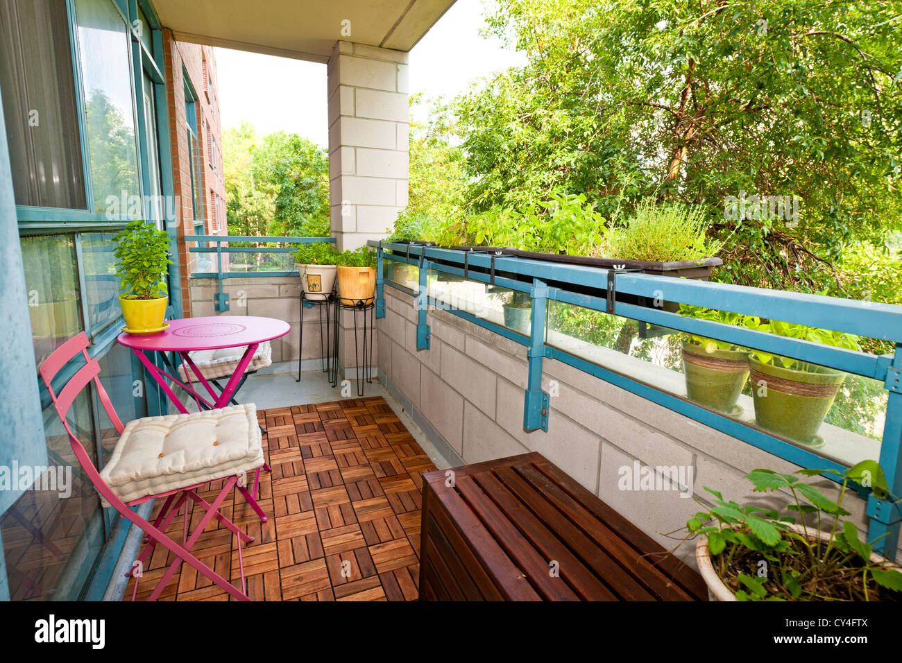 Balcony of condo with patio furniture and plants - Stock Image