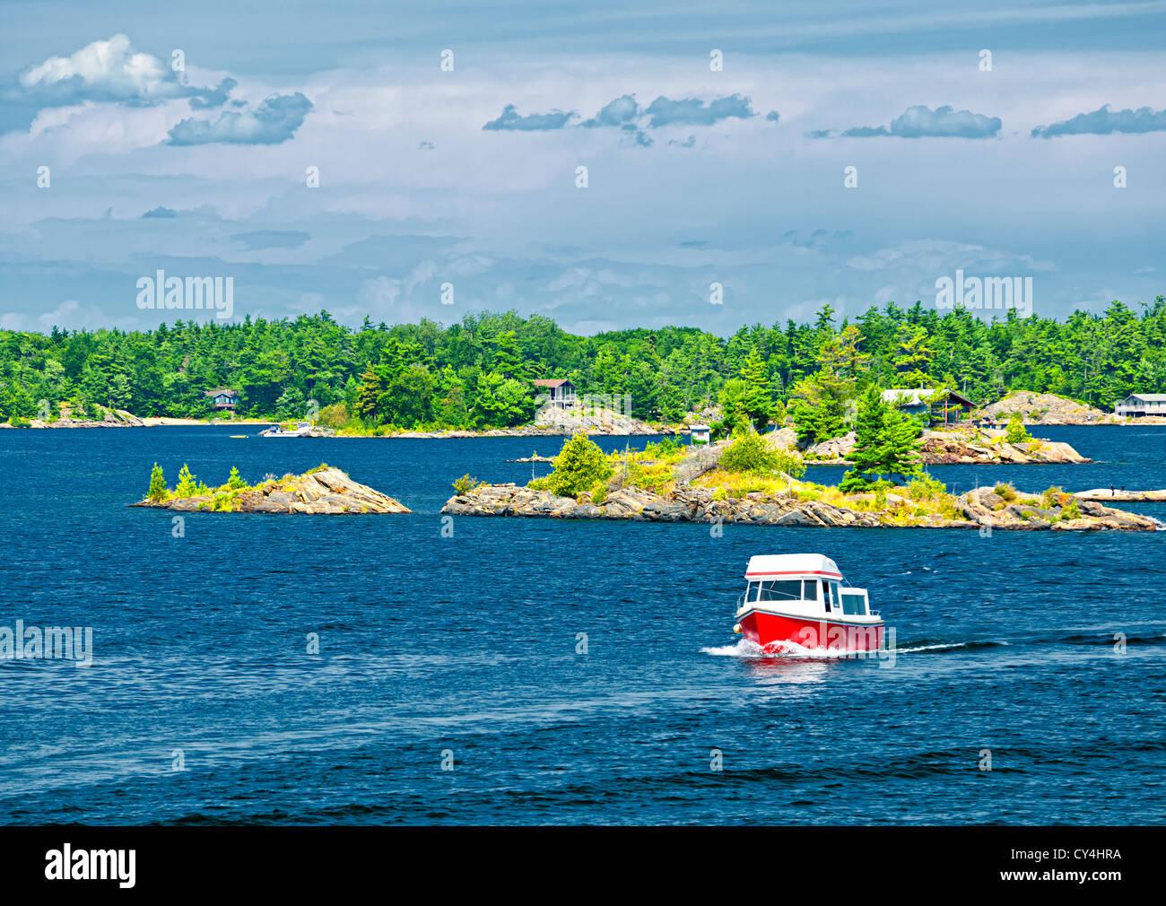 Small boat on lake near island in Georgian Bay, Ontario Canada - Stock Image