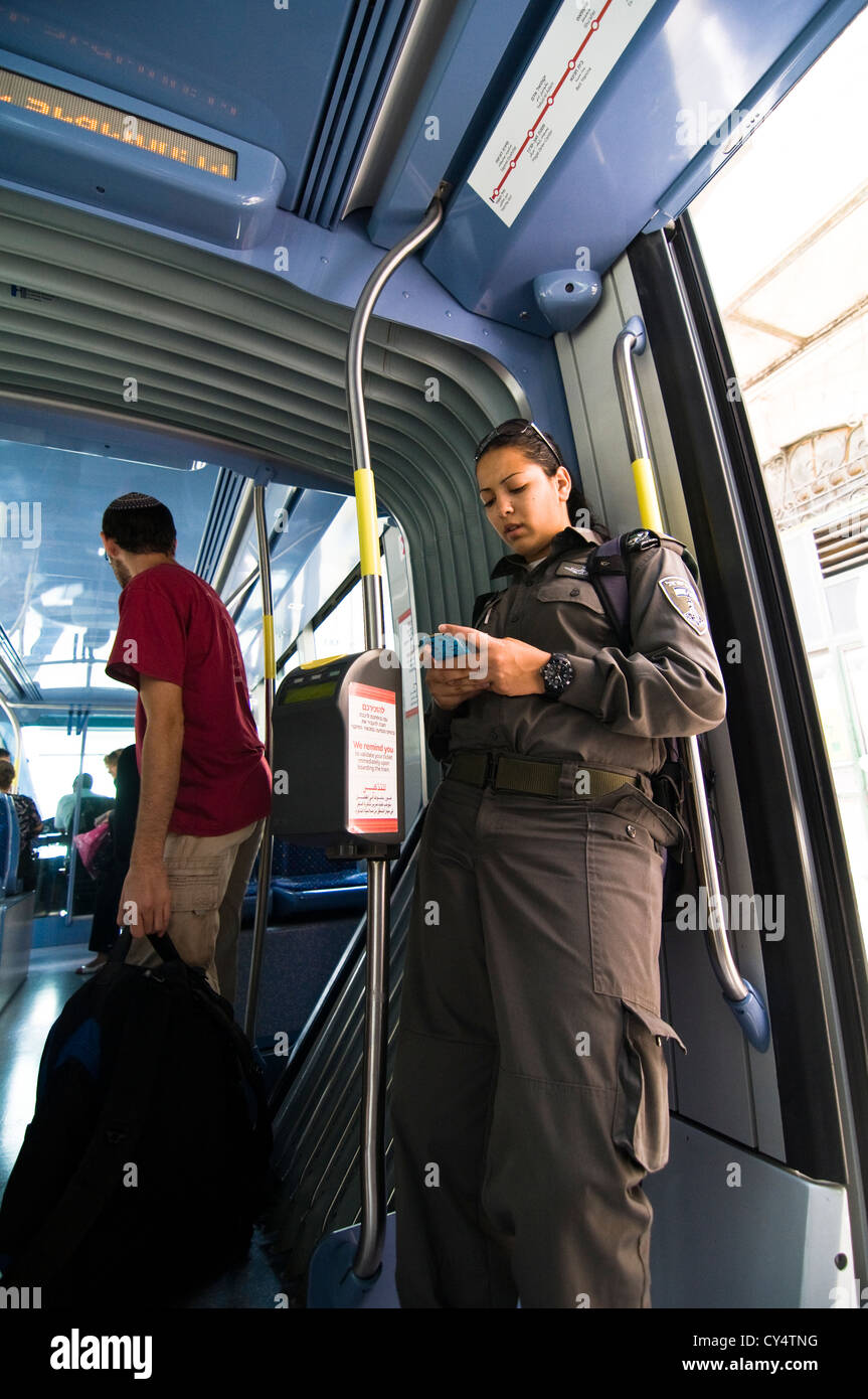 An Israeli border policewoman using her phone in the new tram in Central Jerusalem. - Stock Image