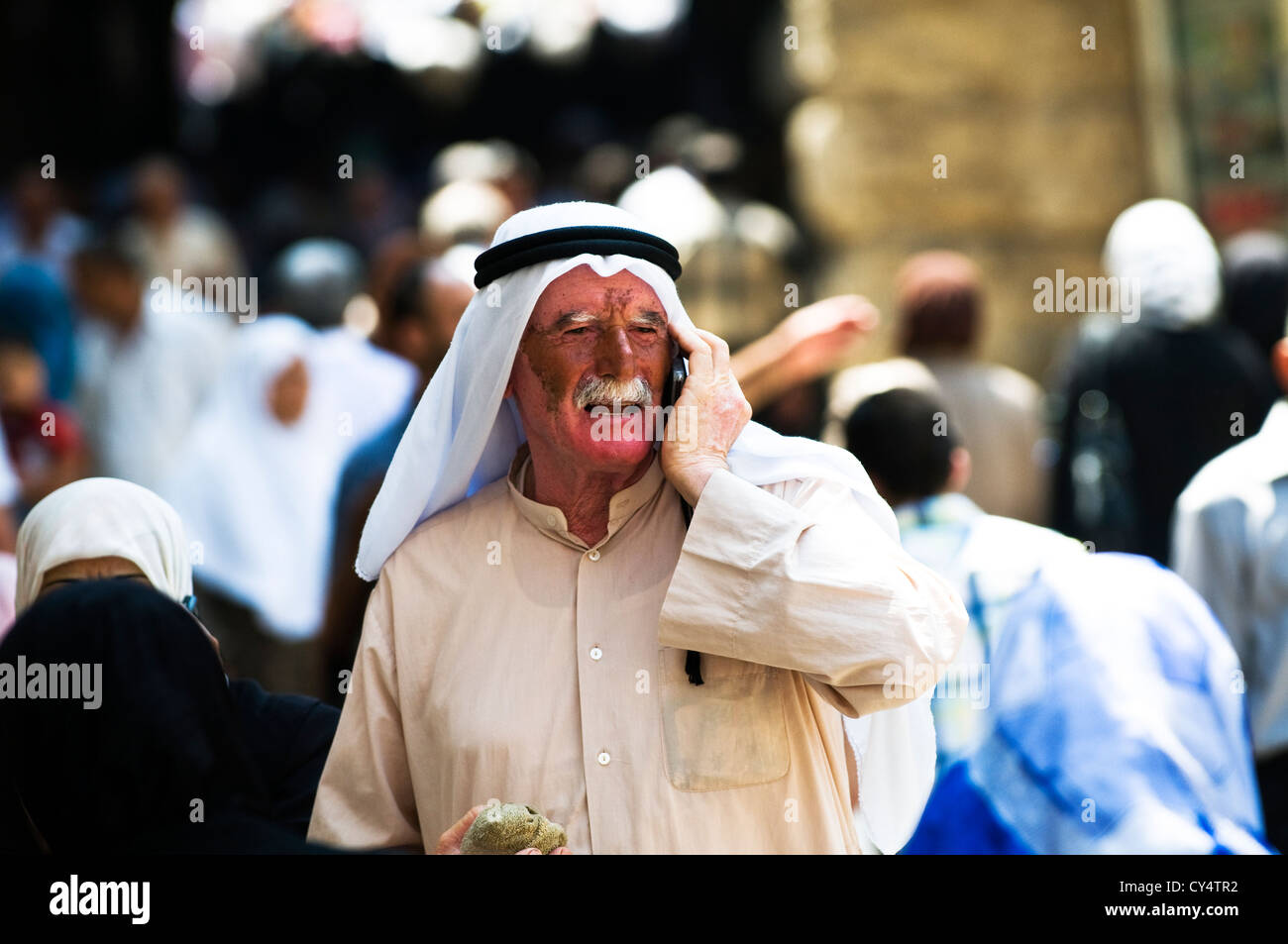 An Arab Palestinian man walking through the narrow streets of the Musim qt in the old city of Jerusalem - Stock Image
