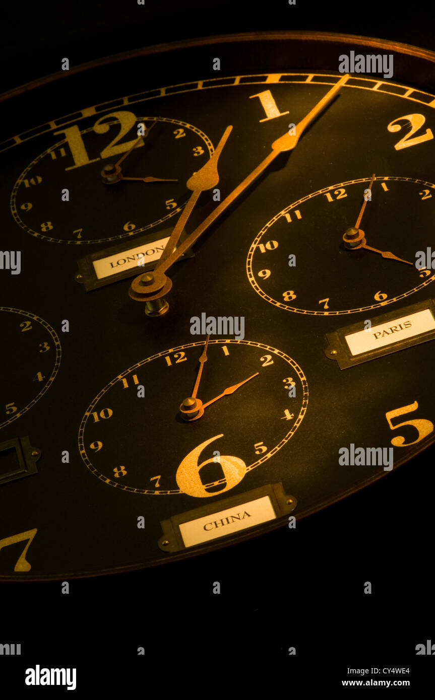 vintage clock with multiple faces depicting time in different parts of the world light painted with flashlight. - Stock Image