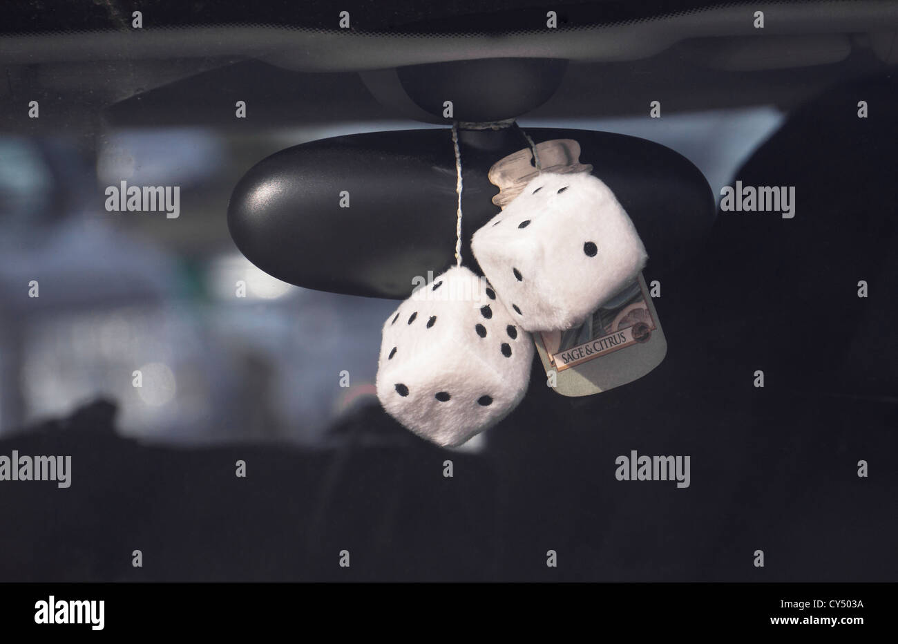 Fluffy dice and air freshener hanging from the rear view mirror of a car. - Stock Image