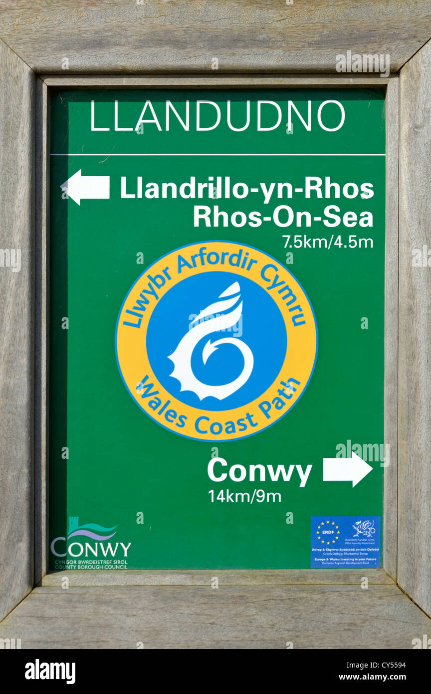 Wales Coast Path multilingual signboard on the seafront promenade at Llandudno between Rhos On Sea and Conwy - Stock Image