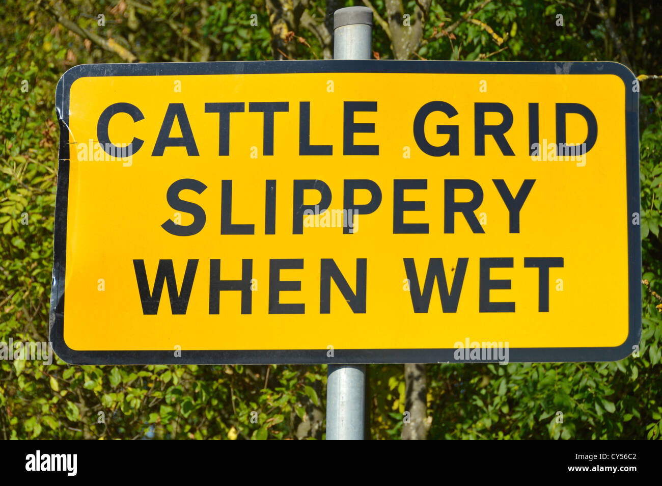 Slippery when wet warning sign on approach to Cattle Grid - Stock Image