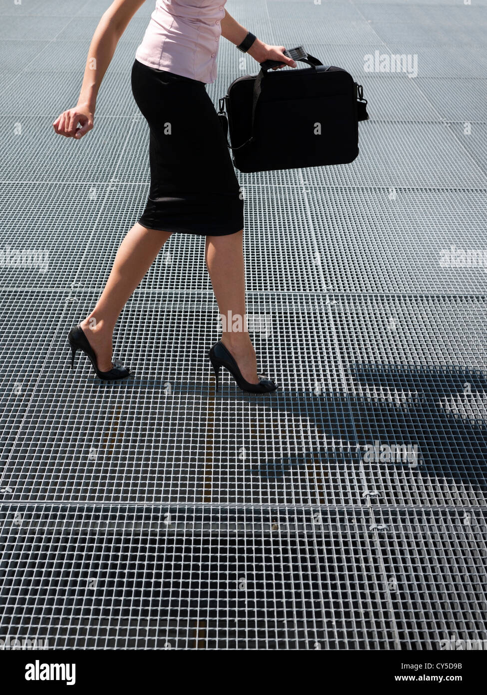 cropped view of mid adult business woman walking on high heels, trying to balance on grating - Stock Image