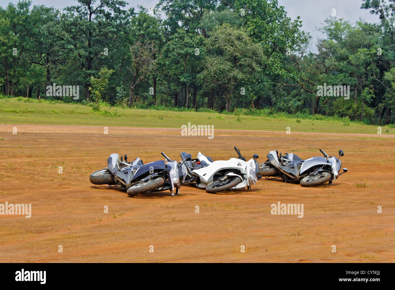 Three generic motorbikes dropped on their side. Concept, play dead they might go away. Location of shot India - Stock Image