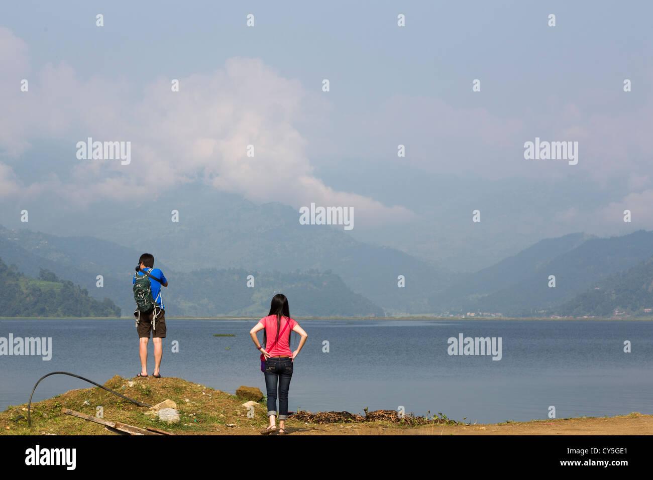 2 tourists enjoy the view of Phewa lake in Pokhara, Nepal - Stock Image