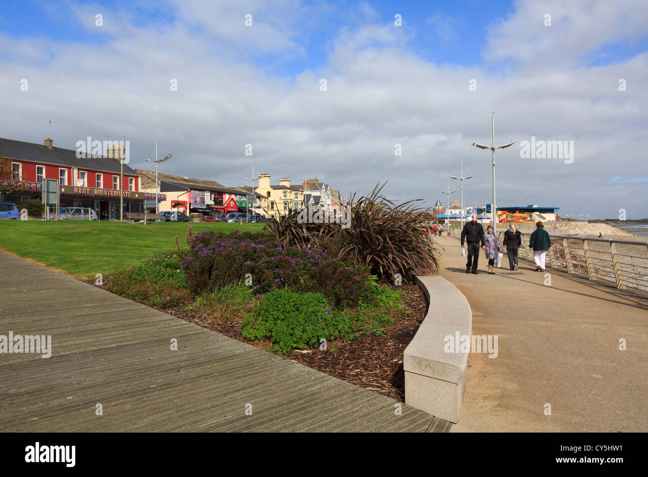 People walking on the seafront promenade of seaside resort on the east coast at Newcastle, Co Down, Northern Ireland, - Stock Image