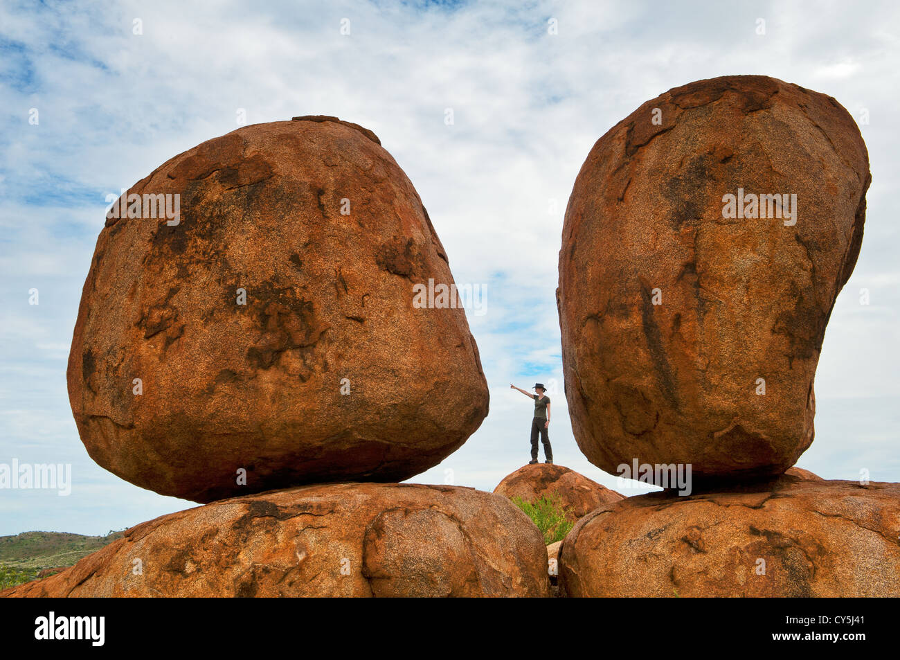 Person in the distance makes the Devils Marbles looking huge. - Stock Image