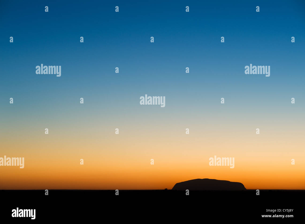 Black silhouette of Uluru in front of a sunlit horizon. - Stock Image
