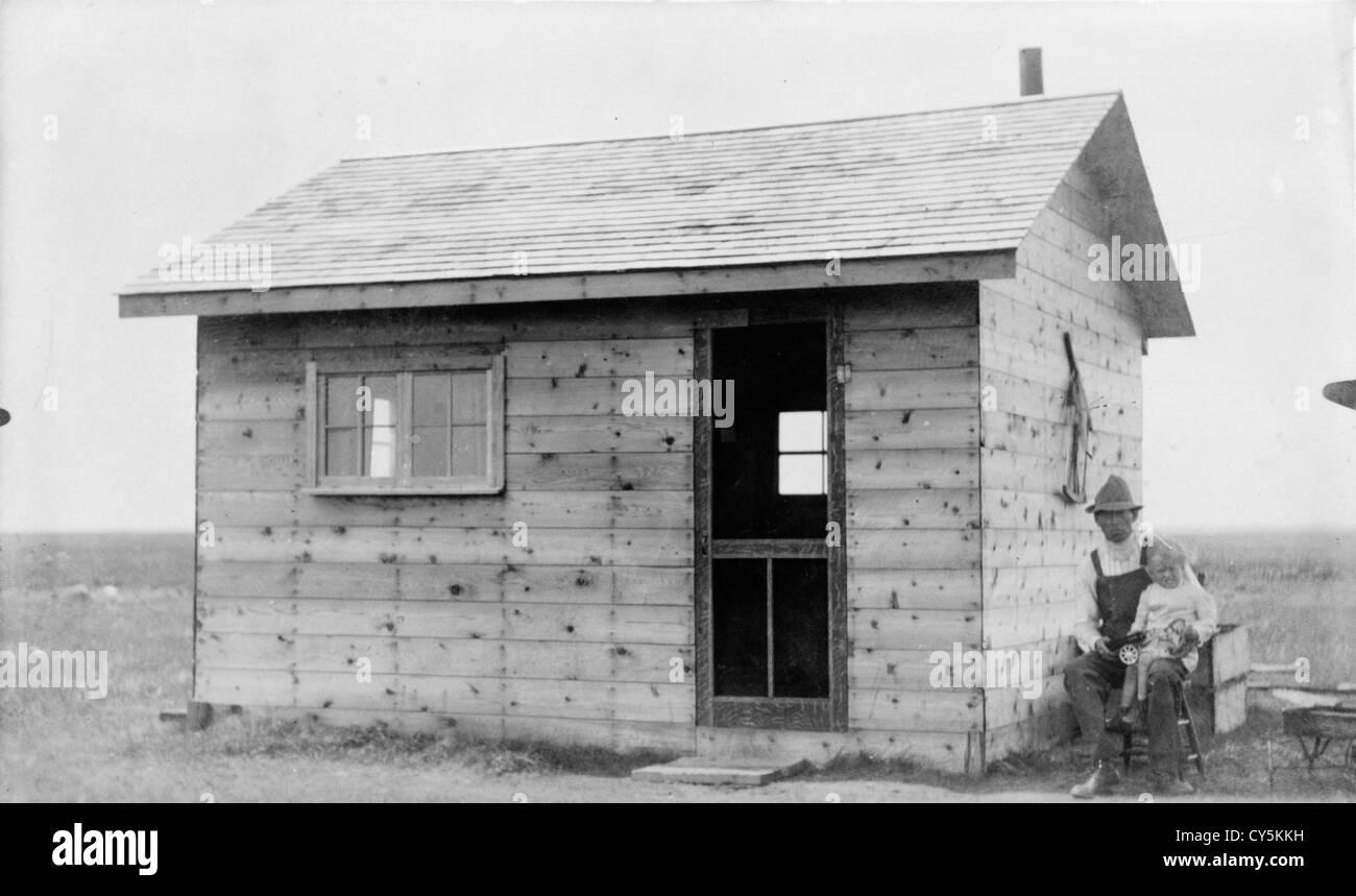 Log timber frame homestead cabin 1900s Canada. Luseland Saskatchewan. HOMER WARWICK SYKES - Stock Image