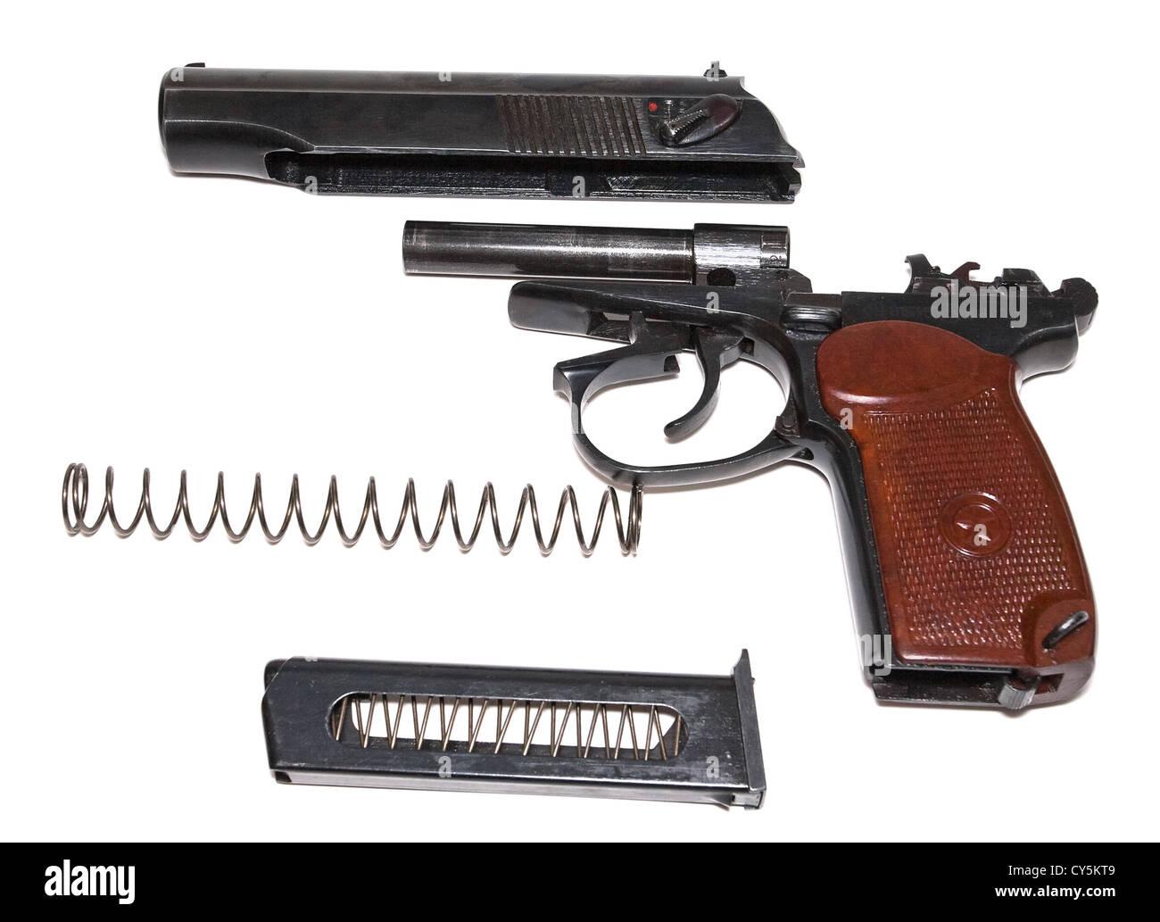 Disassembled handgun on a white background - Stock Image