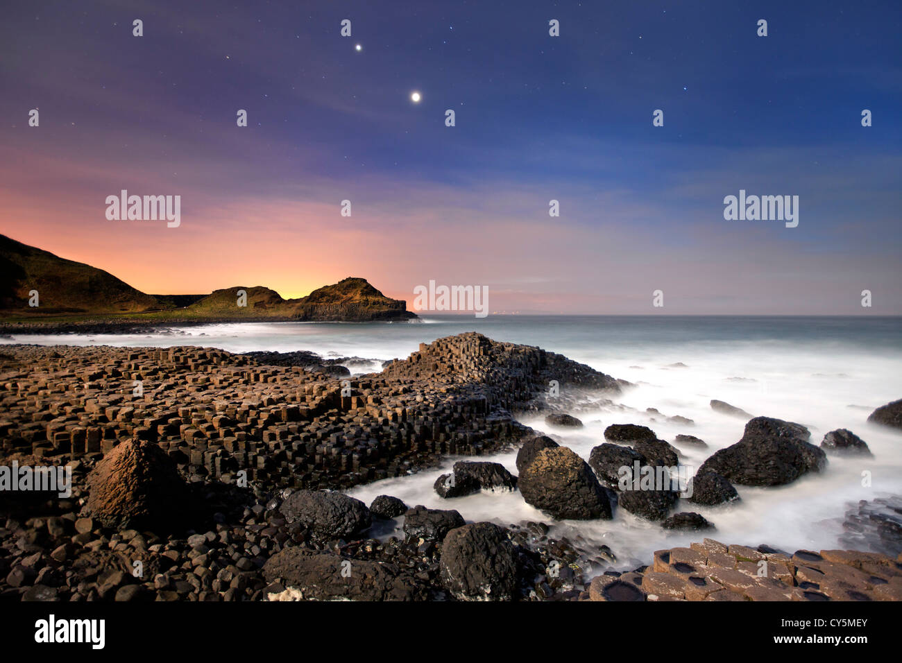 The Giants Causeway at night showing conjunction of Venus and Jupiter in sky. - Stock Image