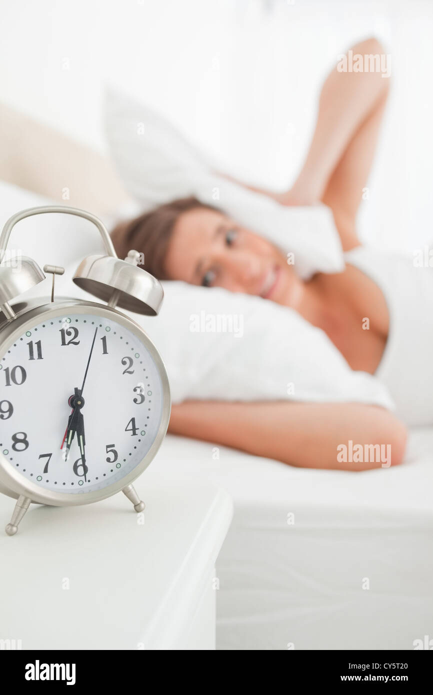 The alarm clock rings loudly as she blocks her ears - Stock Image