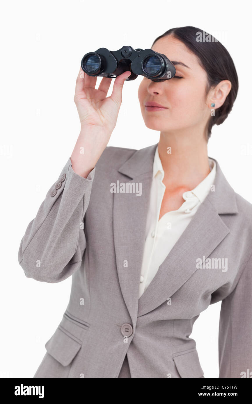 Businesswoman looking through spy glasses - Stock Image