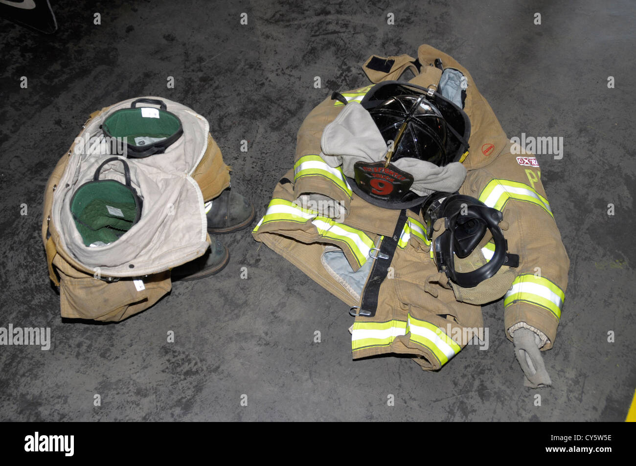 firefighters gear sits on the floor waiting to be used when a call comes in - Stock Image