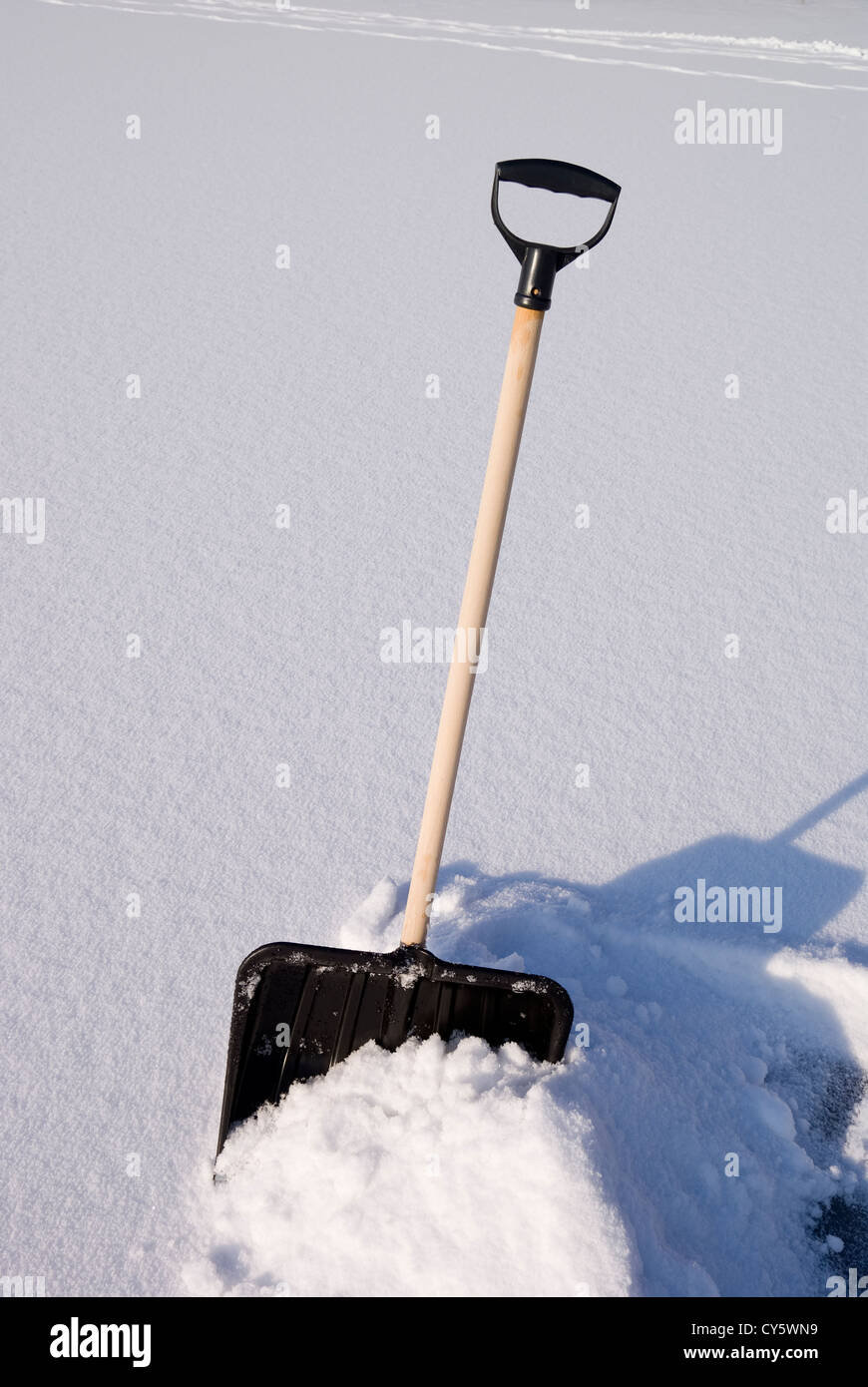 snow shovel on on piled hill snow - Stock Image