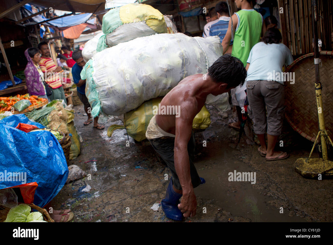 Market traders in Carbon market.A man pulls a  heavy load of vegetables,Cebu City,Philippines - Stock Image
