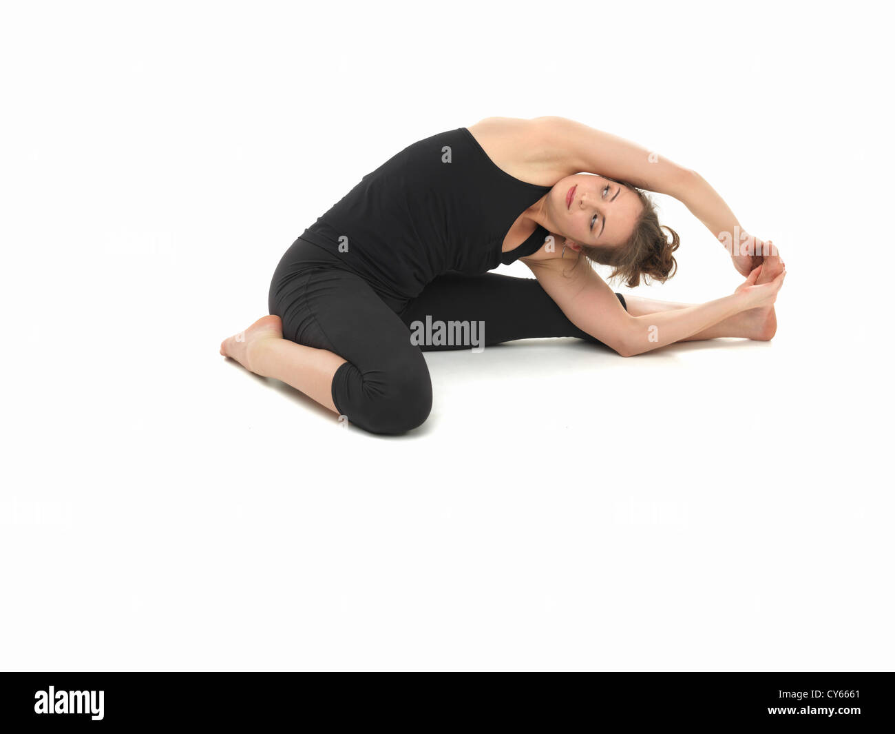 difficult advanced yoga pose by attractive female, on white background, viewed from the front - Stock Image