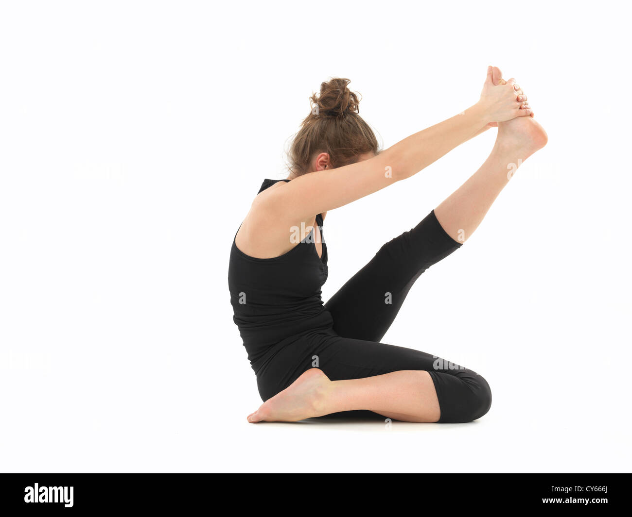 white woman dressed in black, performing difficult yoga pose, body view, on white background - Stock Image
