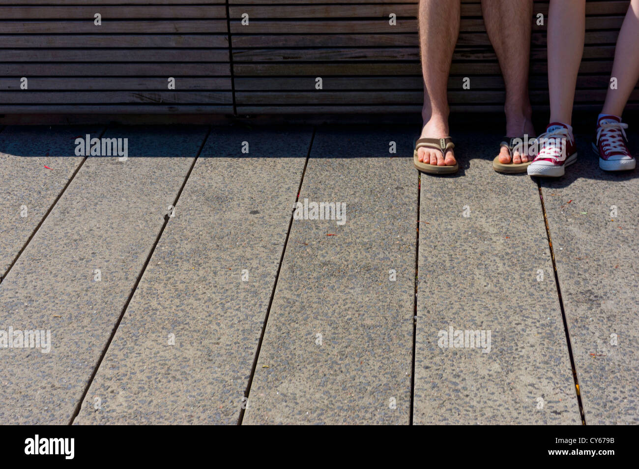 The feet of a young couple wearing summer footwear seated on a bleacher in the High Line city park, Manhattan, New - Stock Image