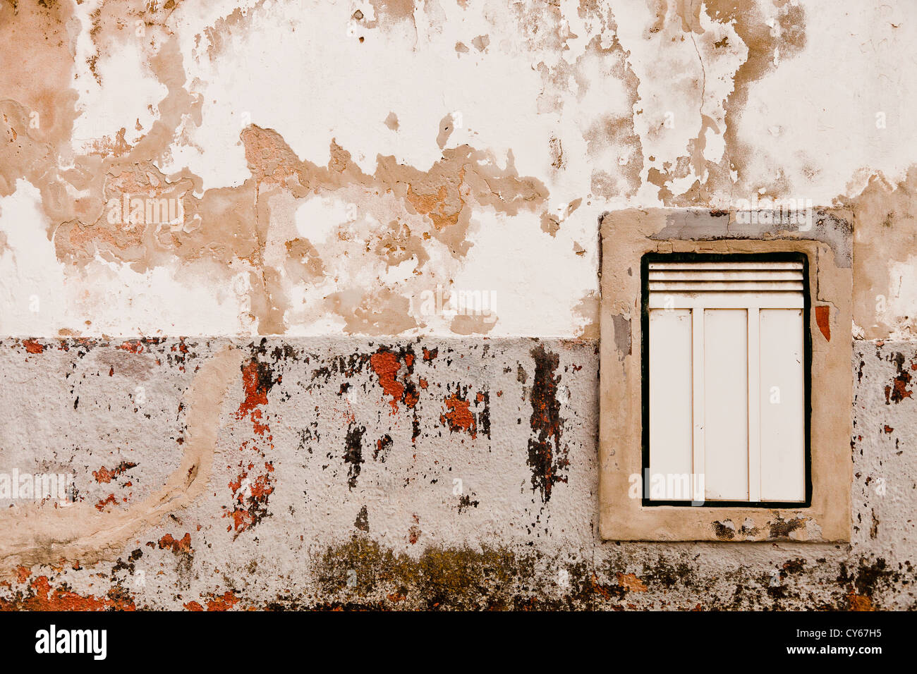 Window on a rendered wall with two tone weather beaten cladding - Stock Image