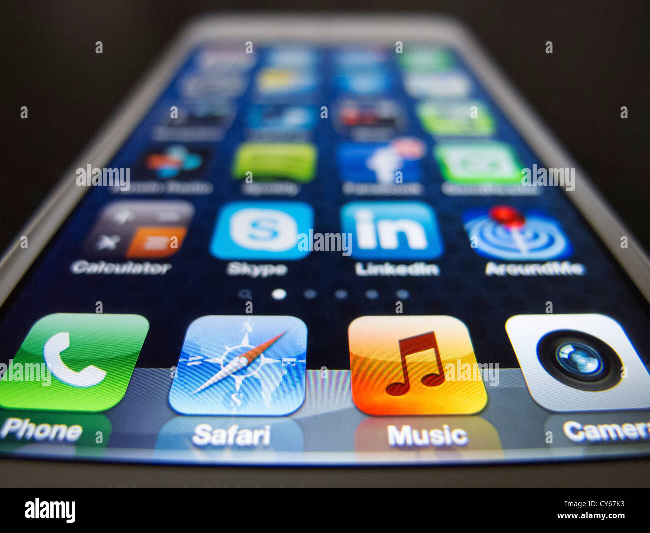 Close-up of new iPhone 5 smart phone showing screen with many apps - Stock Image