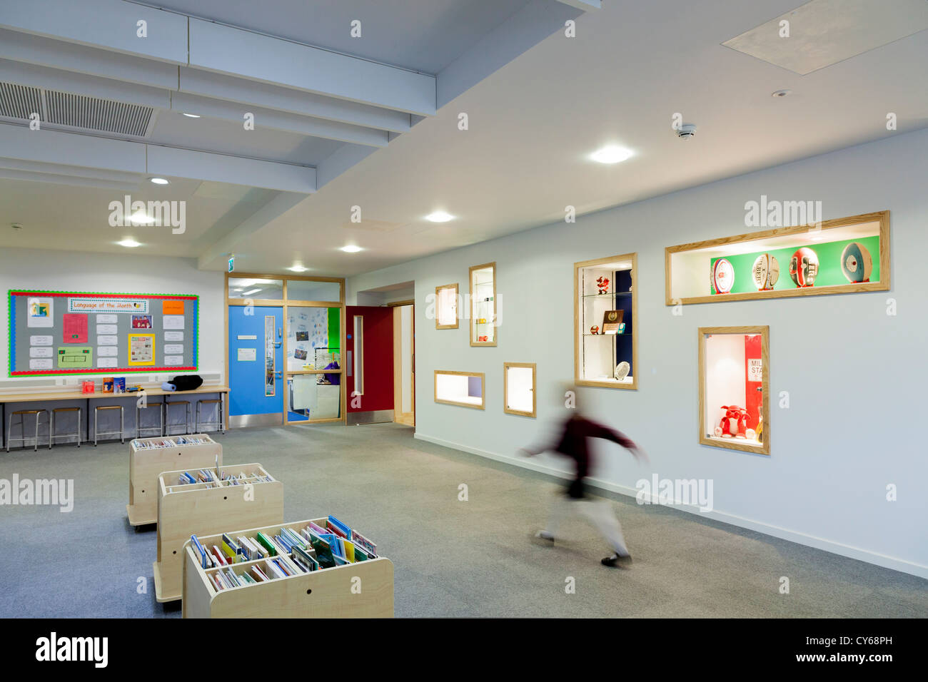 Blurred child walking through library area of primary school. - Stock Image