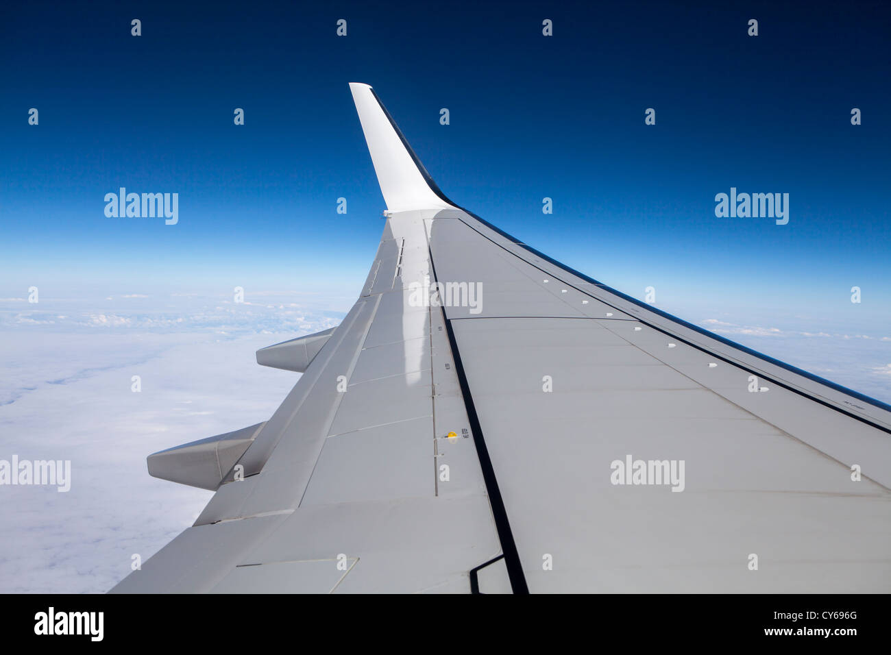 Airplane Boeing-737 wing as seen from a plane window with a bright blue sky. - Stock Image