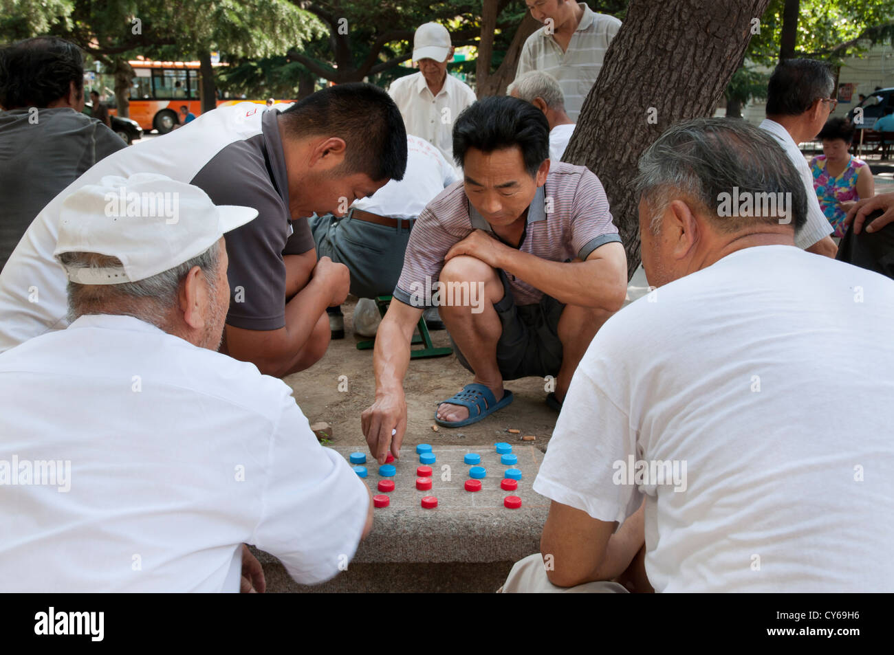 Chinese men play a game of draughts using bottle tops as counters, Qingdao, China - Stock Image