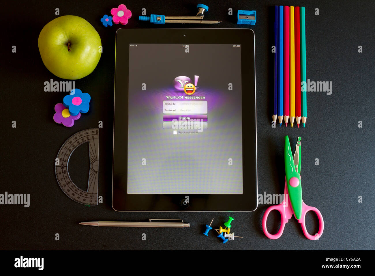 Ipad 3 with school accesories and yahoo messenger on the screen - Stock Image