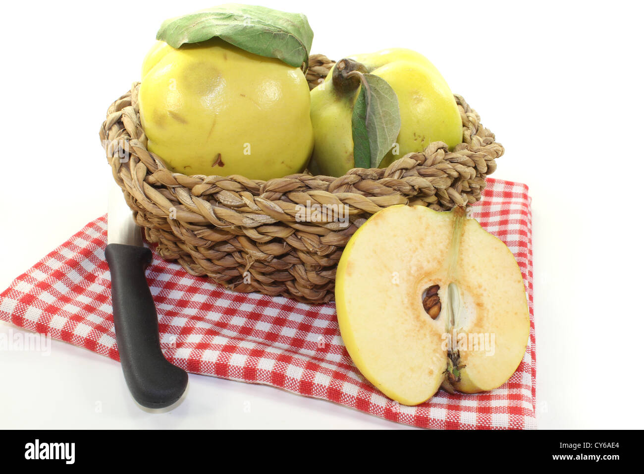 Quinces with leaves in a basket on a light background Stock Photo