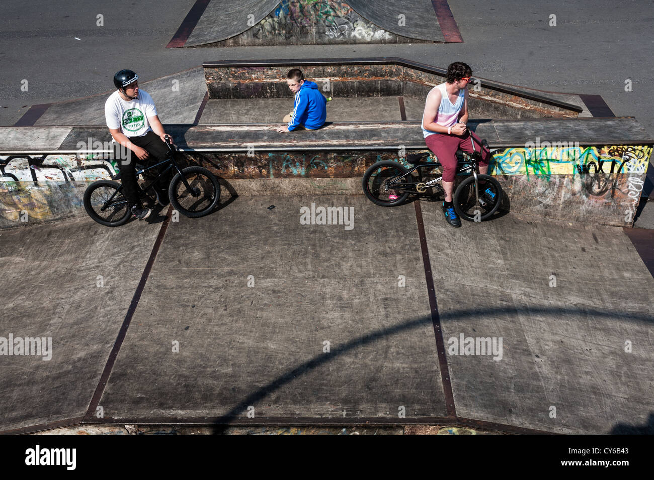 Teenagers riding bikes in a skate park. - Stock Image