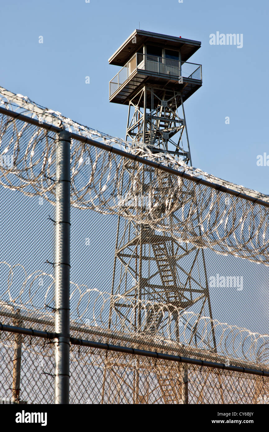 Tower overlooking prison security fence. - Stock Image