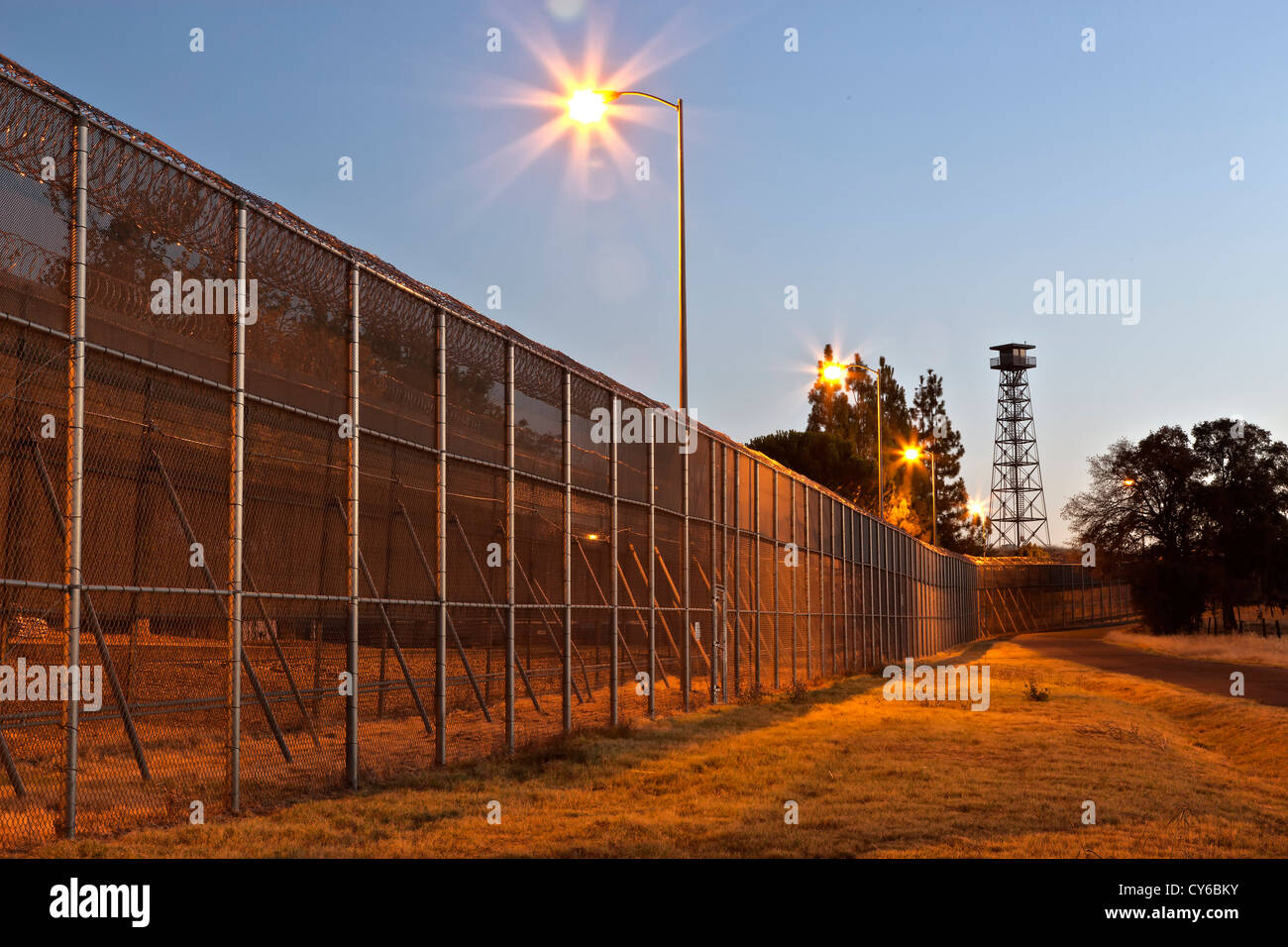 Prison security fence, tower, before sunrise. - Stock Image