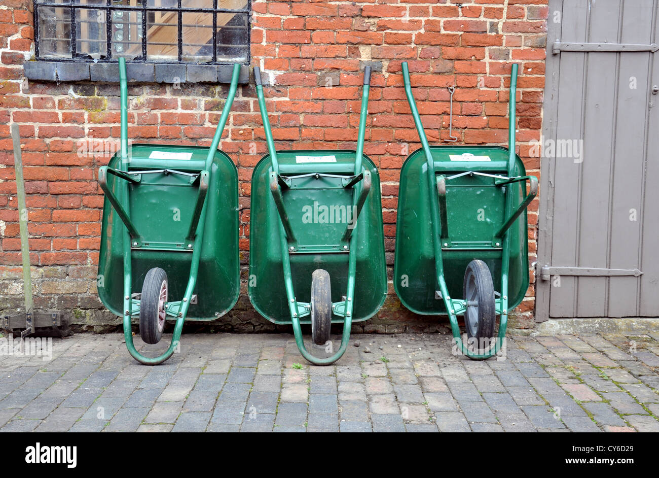Three green wheelbarrows leaning against an outhouse wall - Stock Image