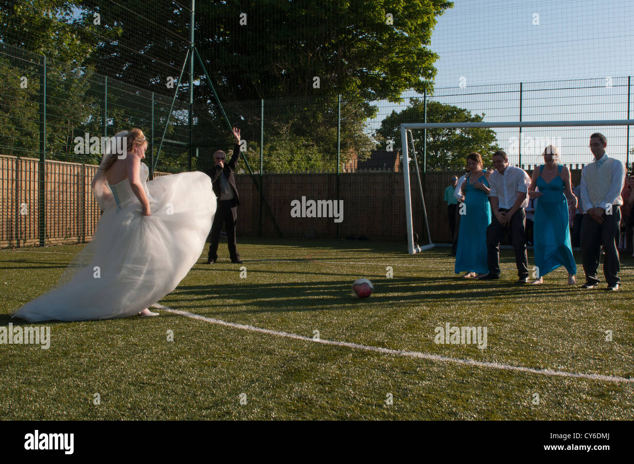 Model Released - quirky shot of a bride playing football at a wedding - Stock Image