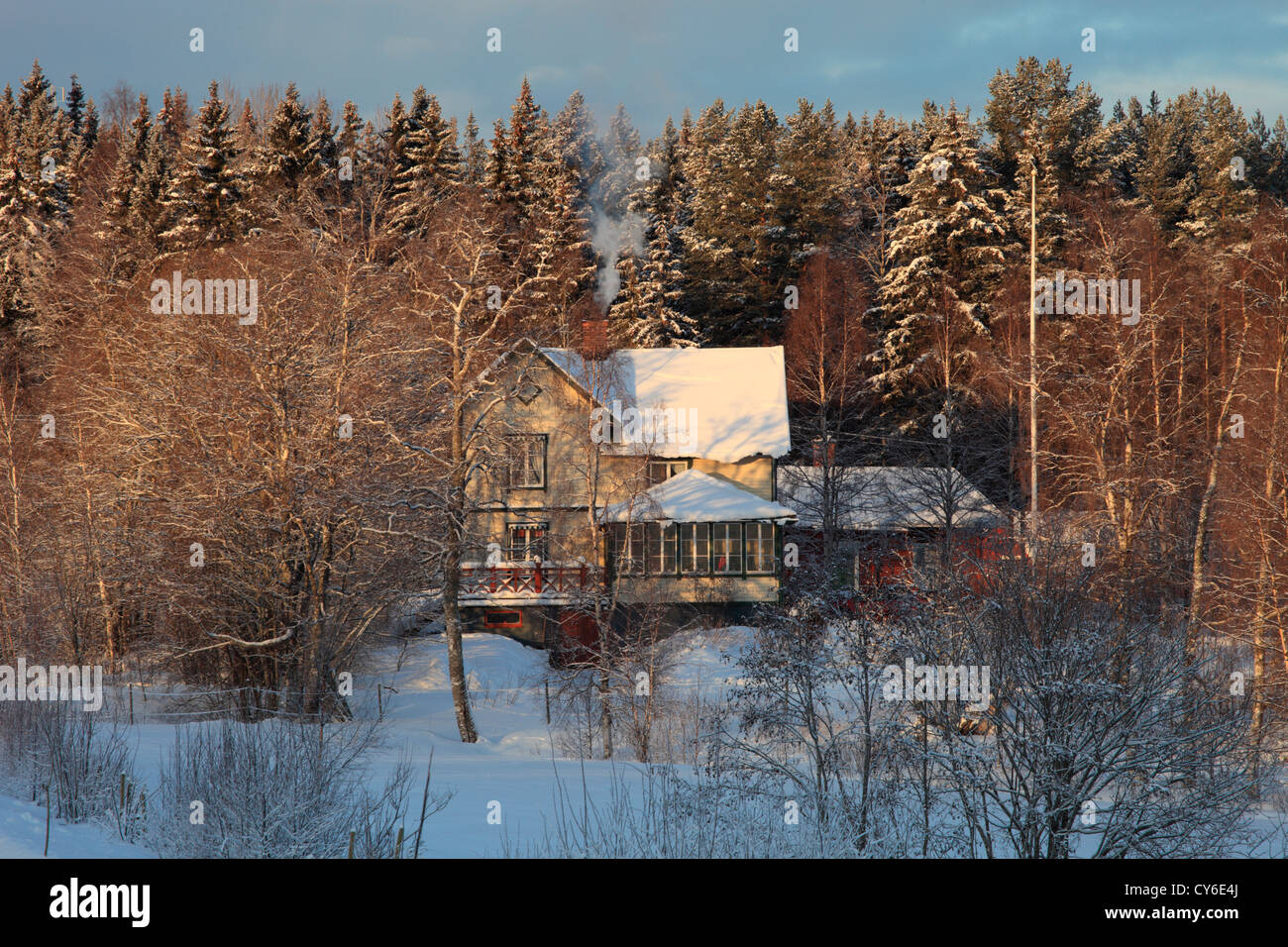 Smoke is curling from the chimney of a yellow wooden house in winter. - Stock Image