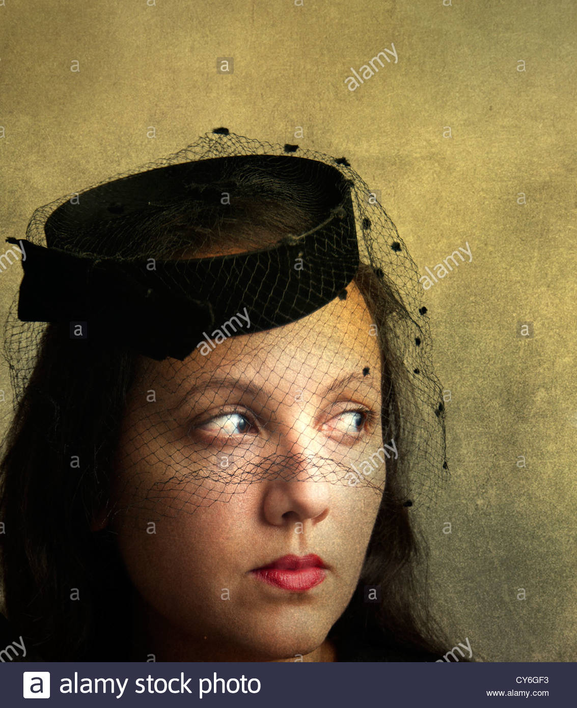 Portrait of mysterious beautiful woman with old fashioned pillbox hat with veil - Stock Image