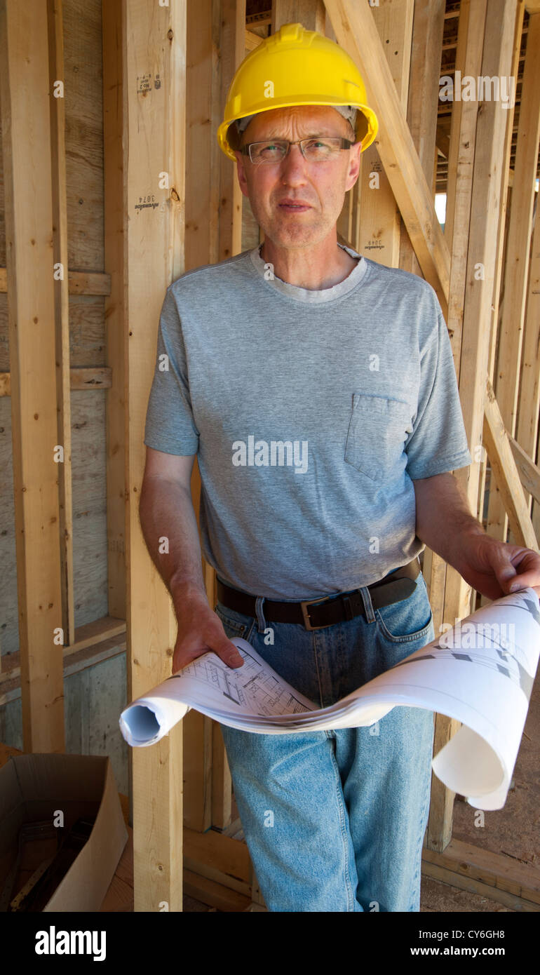 Male construction worker on job site with blueprints in hand and wearing a hardhat - Stock Image