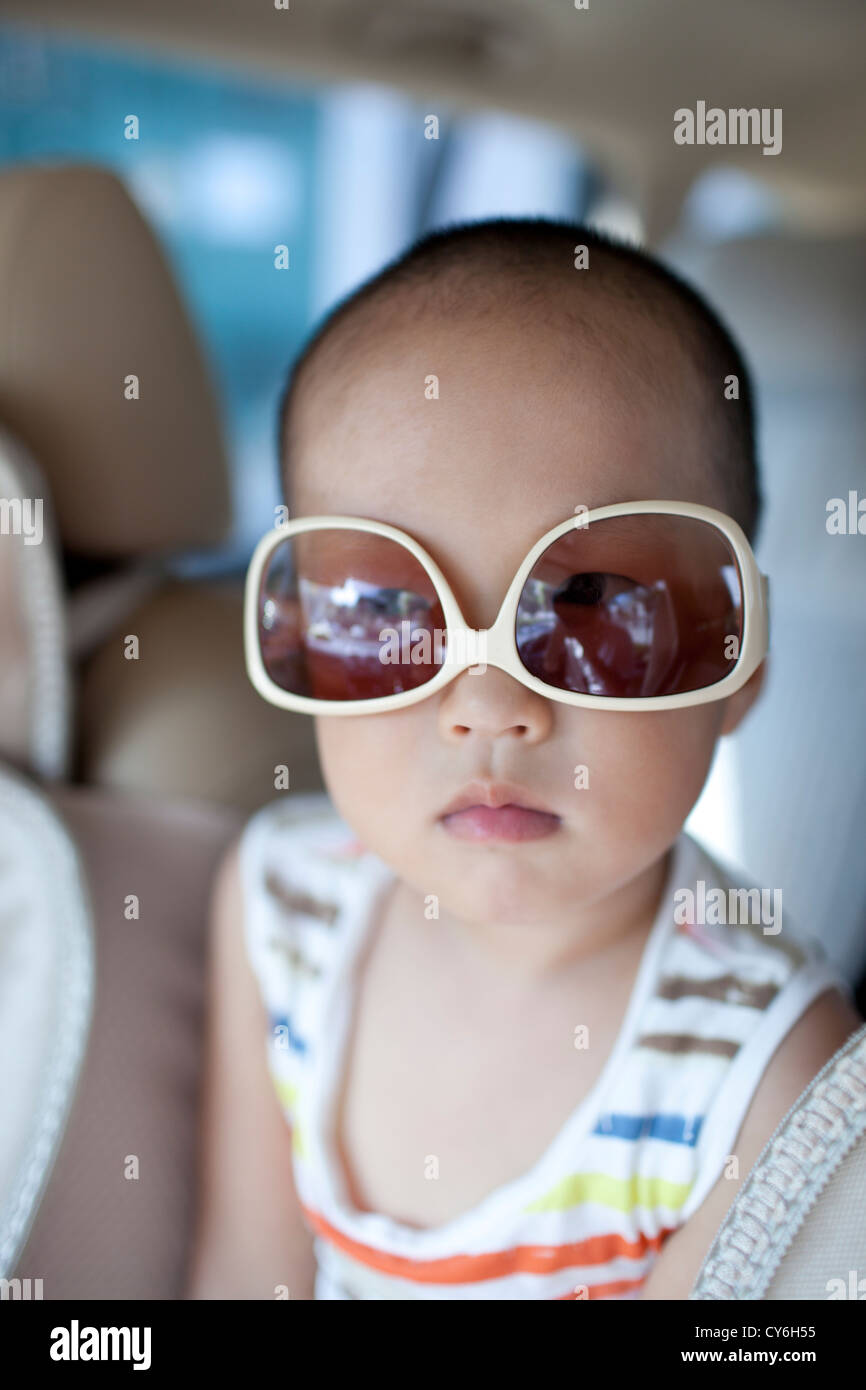 Asian boy wearing sunglass in the car with cute - Stock Image