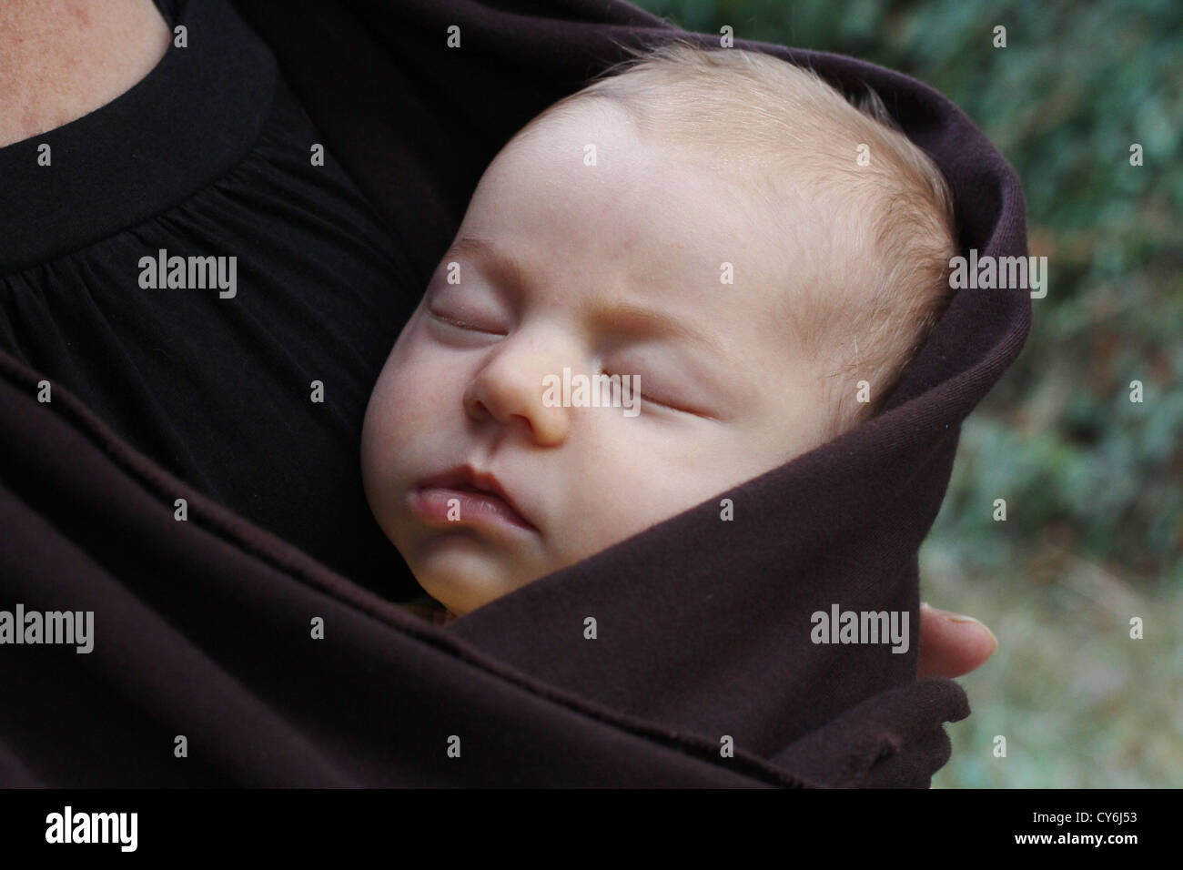 A small baby sleeping while wrapped in a sling. - Stock Image