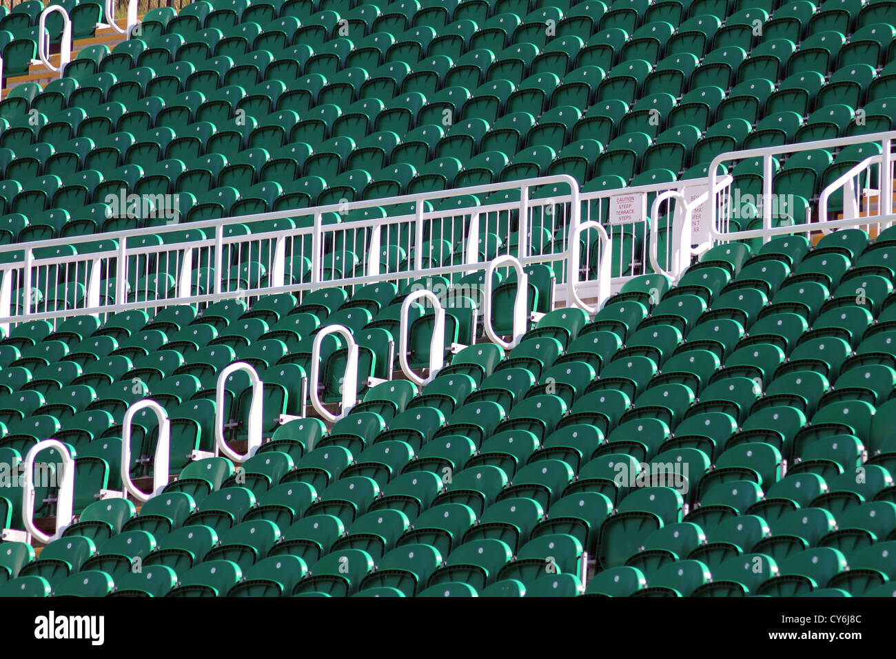 Terrace seating in outdoor stadium or arena with green theme. - Stock Image