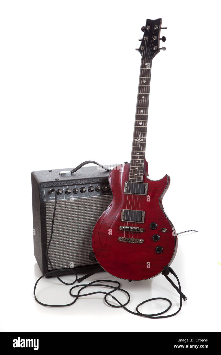 A Electric Guitar On A Stand With An Amplifier And Cords On A White