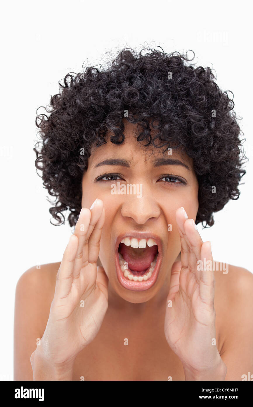 Teenager shouting very loudly against a white background - Stock Image