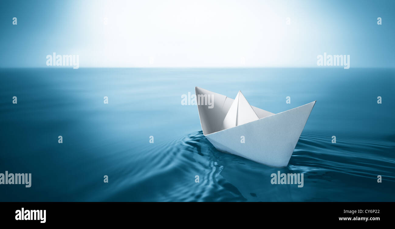 origami paper sailboat sailing on blue water - Stock Image