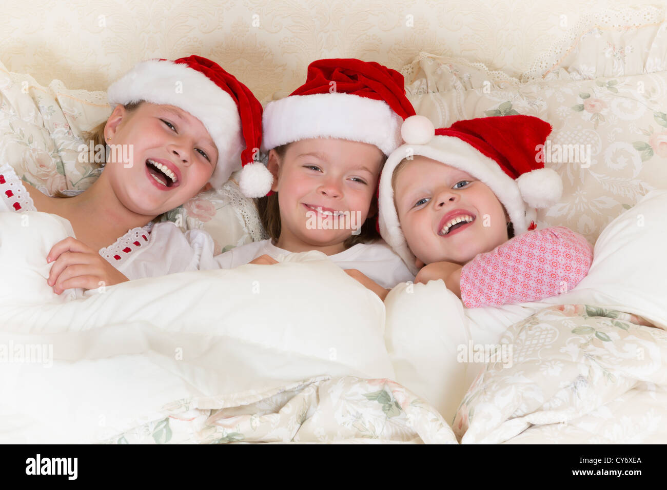 30be503f2 Laughing little girls in bed with santa hats on Stock Photo ...