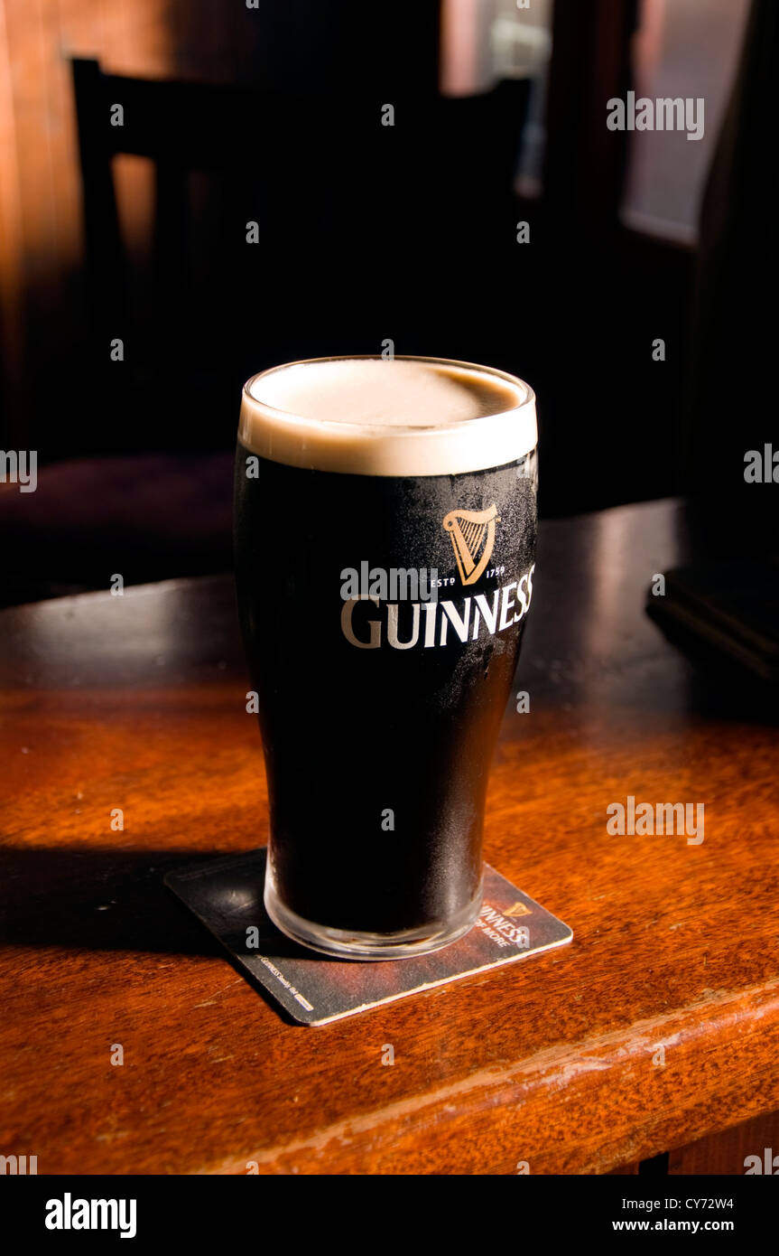 Pint of Irish Stout on a wooden bar - Stock Image